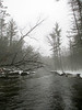 """Misty Water on the Pere Marquette River"" - Daily Photo - 04/05/13  I went on my annual fishing expedition after steelhead a little earlier this year.  My trip was from March 10 through March 15, when for the last twenty years it has been typically the third or fourth week.  Therefore, I knew I was taking chances with  the weather.  The first day it rained on and off, creating a mist more beautiful than what is captured in this picture.  Rain was light and the temperature was around 40 degrees, so it was not unpleasant and I was adequately covered in a rain jacket.  My gear entailed a 7 weight 10 foot Orvis TLS Power Matrix, floating line, 4x fluorocarbon tippet, multiple tungsten beads on a  green caddis nymph (depth charger), egg fly and no net.  Only landed one brown about 18 inches, but was still a lot of fun."
